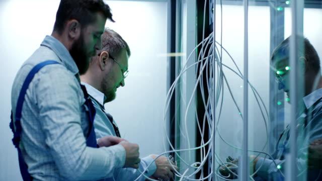 två manliga tekniker som arbetar i ett datacenter - server room bildbanksvideor och videomaterial från bakom kulisserna