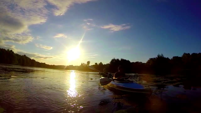 Two male tourists paddling kayak at sunset, beautiful landscape video
