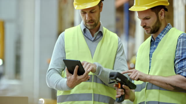 Two male warehouse supervisors comparing inventory data on the scanner and digital tablet video