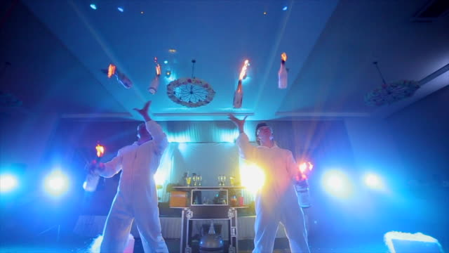 2 人の男性バーテンダーの燃えるようなボトルをジャグリング - バーテンダー点の映像素材/bロール