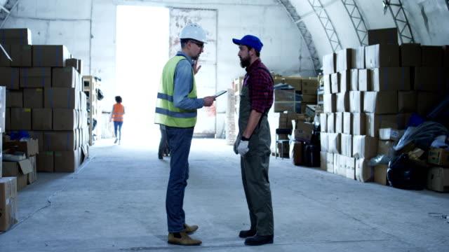 två man diskuterar i ett lager - kameraåkning på räls bildbanksvideor och videomaterial från bakom kulisserna