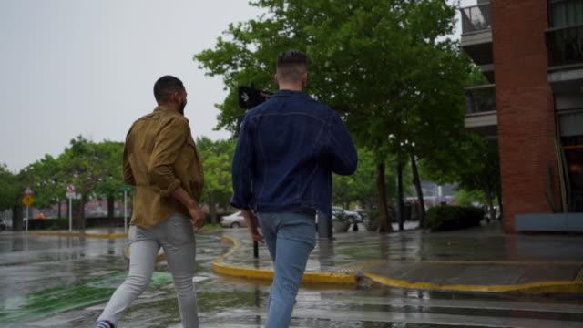 zwei männer halten hände und gehen bei regen - gay man stock-videos und b-roll-filmmaterial
