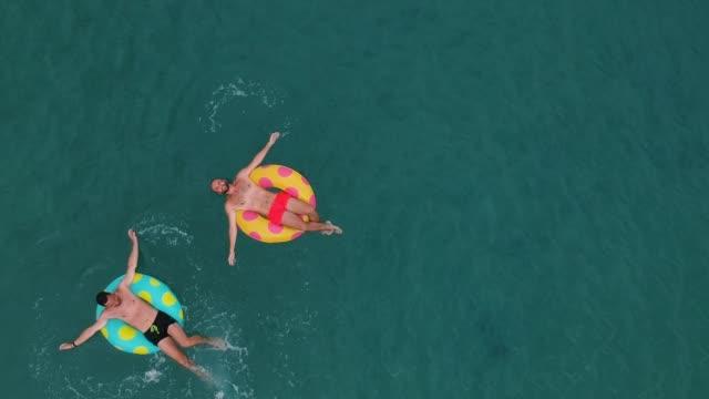 stockvideo's en b-roll-footage met twee man ontspannen op opblaasbare ringen - opblaasband