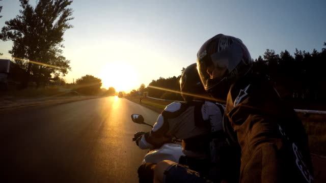 Two man rides on motorcycle at country road in high speed at sunset. Friends going on bike forward to the sun in high speed and making selfie. Pov Close up Two man rides on motorcycle at country road in high speed at sunset. Friends going on bike forward to the sun in high speed and making selfie. Pov Close up action movie stock videos & royalty-free footage