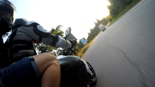 Two man rides on motorcycle at country road in high speed at sunset. Friends going on bike forward to the sun in high speed. Low angle of view Pov Close up Two man rides on motorcycle at country road in high speed at sunset. Friends going on bike forward to the sun in high speed. Low angle of view Pov Close up action movie stock videos & royalty-free footage