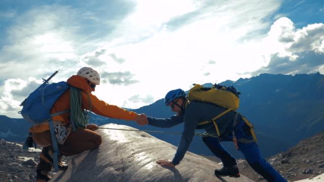 due uomini arrampicata su roccia - in cima video stock e b–roll