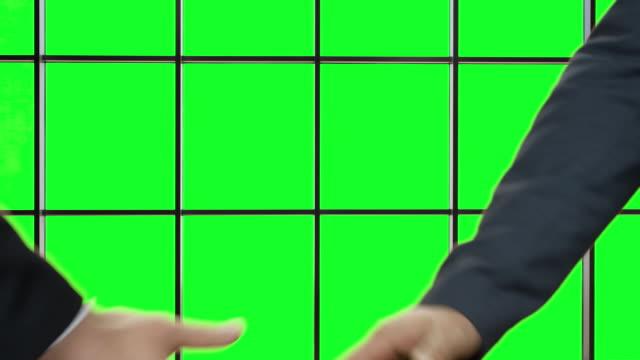 Zwei Mann Händeschütteln auf grünem Hintergrund. – Video