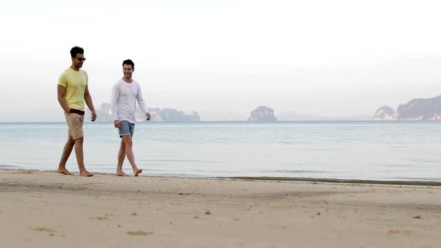 zwei mann zu fuß am strand, im gespräch, gay paar kommunikation touristen am meer - gay man stock-videos und b-roll-filmmaterial