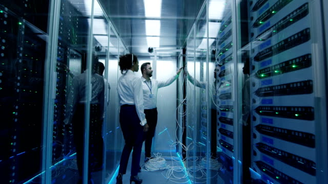 Two managers check server hardware Diverse employees in the data center in the server room discuss server operation. server room stock videos & royalty-free footage