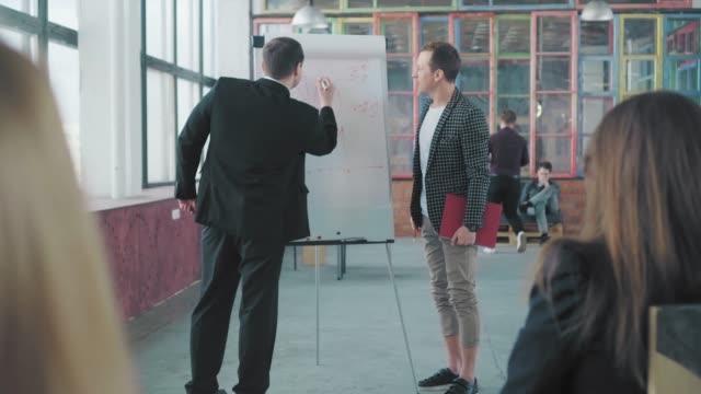 2人のマネージャーがフリップチャートの近くで聴衆にプレゼンテーションを開催し、チャートを描いて話し合います。クリエイティブなオフィスインテリア。コワーキングチーム。オフィス ビデオ