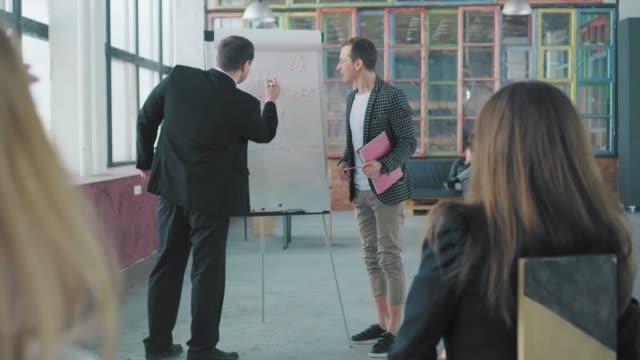 2人のマネージャーがフリップチャートの近くで聴衆にプレゼンテーションを行い、話し合います。クリエイティブなオフィスインテリア。コワーキング。オフィスチーム ビデオ