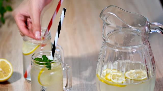two mason jar glasses of homemade lemonade on a wooden background. - paglia video stock e b–roll