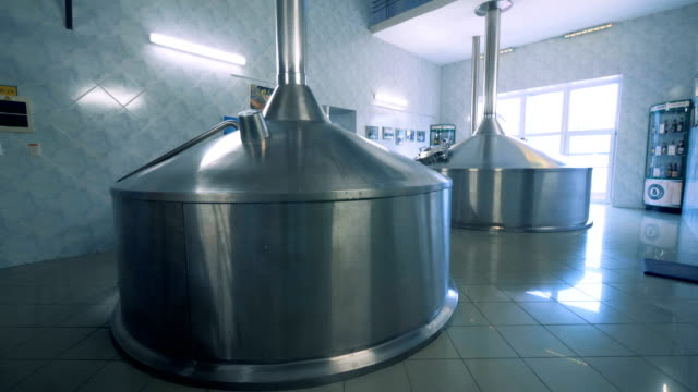 two massive canisters placed in a hall of a brewery factory - vodka video stock e b–roll