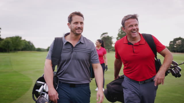 zwei reife paare spielen golf walking entlang fairway tragen golftasche - golf stock-videos und b-roll-filmmaterial