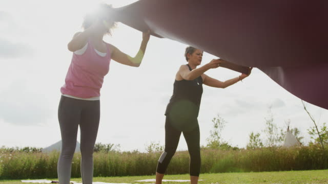 two mature female friends laying out exercise mats on grass at outdoor yoga retreat - tappetino video stock e b–roll