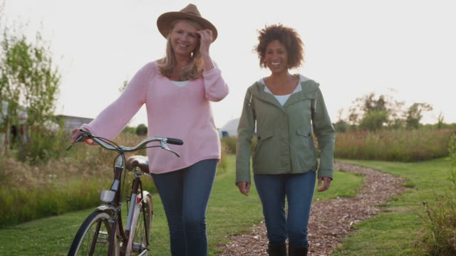 Two Mature Female Friends Walking Along Path With Bike Through Yurt Campsite Two mature female friends walking along path pushing bike on yurt campsite - shot in slow motion human age stock videos & royalty-free footage