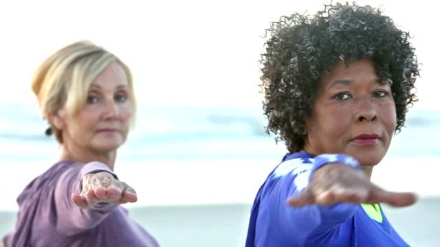Dos mujeres maduras haciendo yoga en la playa - vídeo