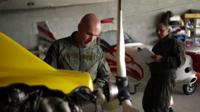two mechanics test airplanes - часть машины стоковые видео и кадры b-roll