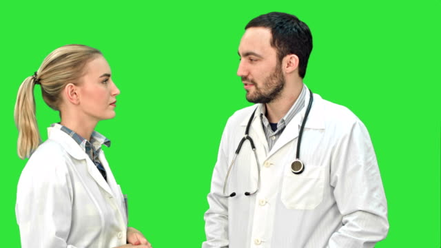 Two medical professionals discuss with a patient on a Green Screen, Chroma Key video