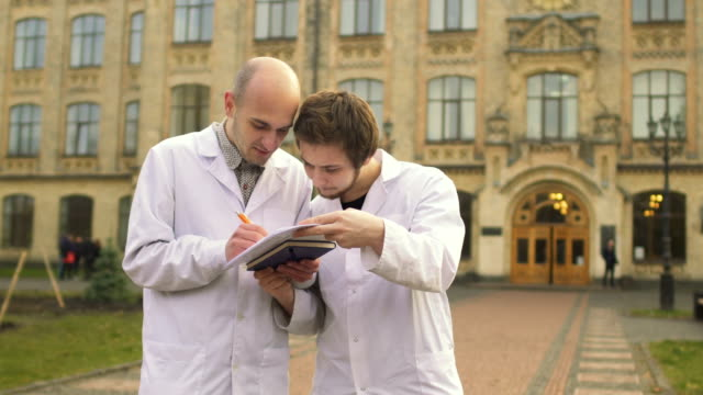 Two medical students in bathrobes discuss something at campus background video