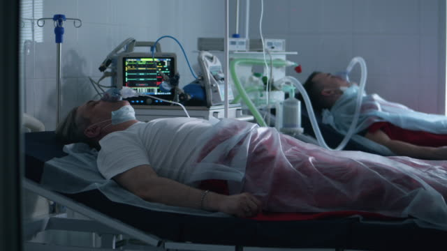 Two men are lying in a hospital and breathing with a ventilator. Coronavirus, covid-19 infected patients in a clinic.