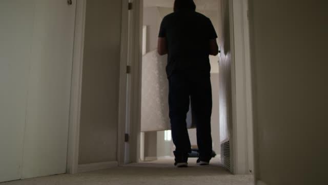 Two Men Carry a Mattress Down a Hallway