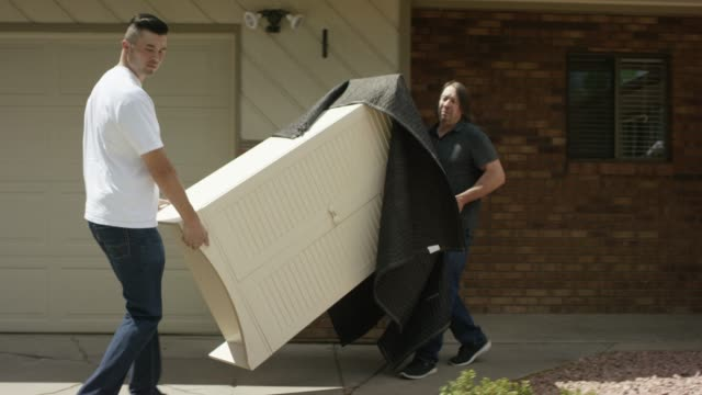 two men carry furniture out to a moving van - portare video stock e b–roll