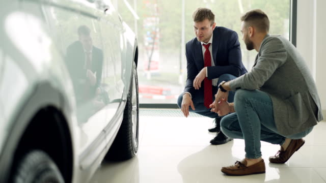 Two men cheerful customer and friendly salesman are talking and gesturing discussing car model while squatting near expensive automobile. Buying and selling vehicles concept. Two handsome men cheerful customer and friendly salesman are talking and gesturing discussing car model while squatting near expensive automobile. Buying and selling vehicles concept. car salesperson stock videos & royalty-free footage