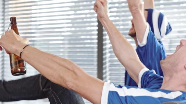 vídeos de stock e filmes b-roll de two men cheering in front of tv - equipamento desportivo