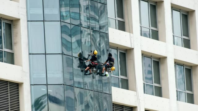 Two men cleaning personnel are hanging with wire safety belt to wipe windows mirror video