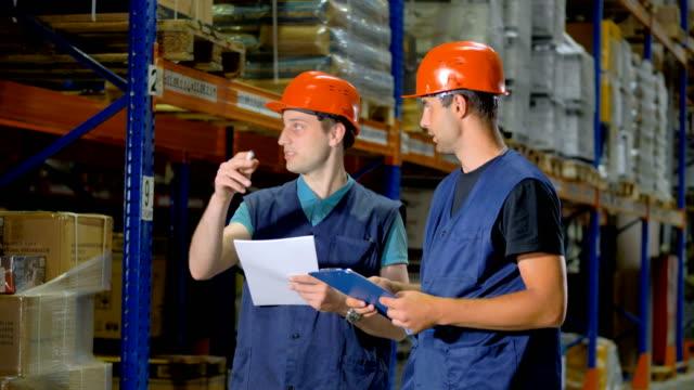 vídeos y material grabado en eventos de stock de dos hombres discuten cuestiones de trabajo dentro de un gran almacén. - gerente de cuentas