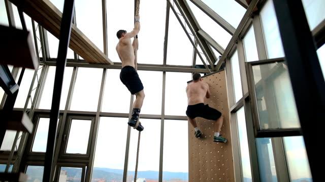 two men doing climbing exercise - inerpicarsi video stock e b–roll