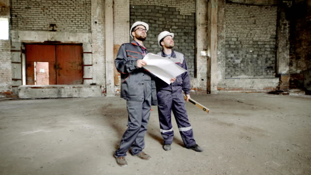 Two men dressed in uniform and safety hardhats are standing on building site and looking over working area. Foreman is holding contsruction plan. Builder is holding spirit level video