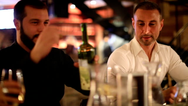 Two men drinking wine in the bar and laughing