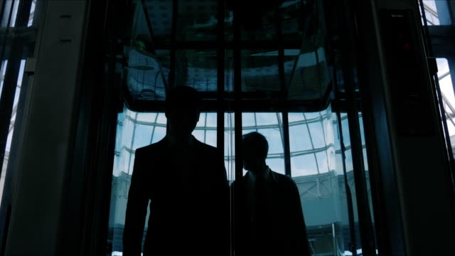 Two men emerge from the glass elevator video
