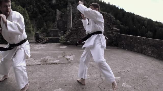 ws two men fighting karate on kamen castle / begunje na gorenjskem, slovenia - karate stok videoları ve detay görüntü çekimi