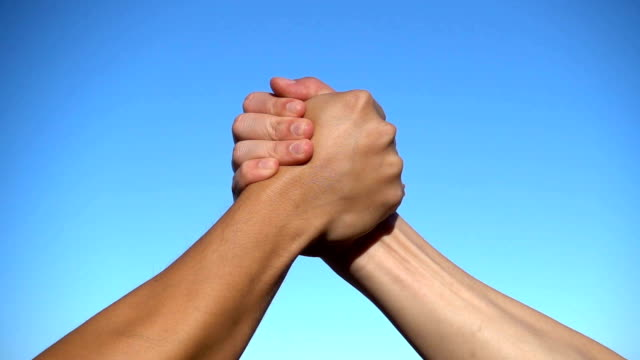 slow mo cu two men hands having sport arm-wrestle handshake - rivalità video stock e b–roll