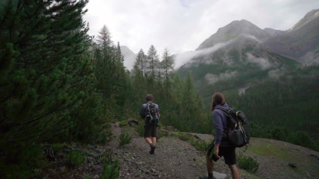 Two men hike wooded trail in mountains