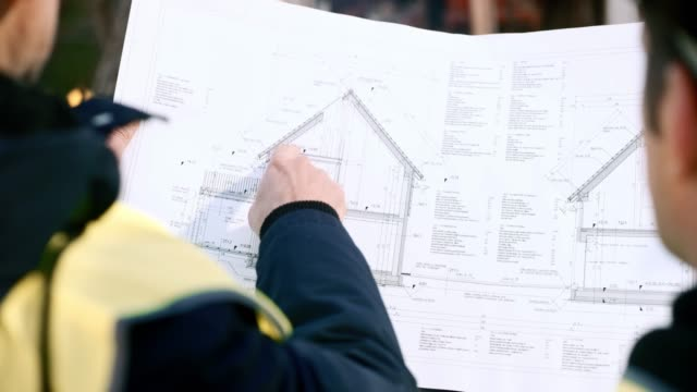 Two men holding up the plan for a house and talking about it