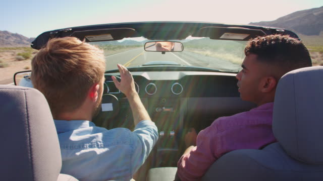 Two Men In Convertible Car Driving Along Road Shot On R3D video
