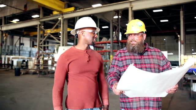 Two men in factory looking at floor plans video