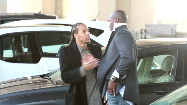 Two men in parking lot look at phone, shake hands, leave video