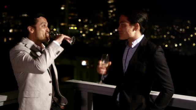 vidéos et rushes de deux hommes en costumes et boire tout en parlant sur le toit à la nuit tombée. un autre approche lui, pose une question et ils laisser - man drinking terrace