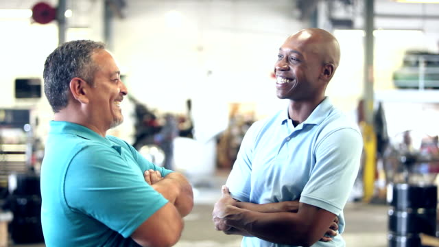 Two men in truck repair shop talking Two multi-ethnic workers in the trucking industry, standing in a garage, talking. The older man, in his 40s, is Hispanic. His co-worker is African-American. A semi-truck is out of focus in the background. face to face stock videos & royalty-free footage