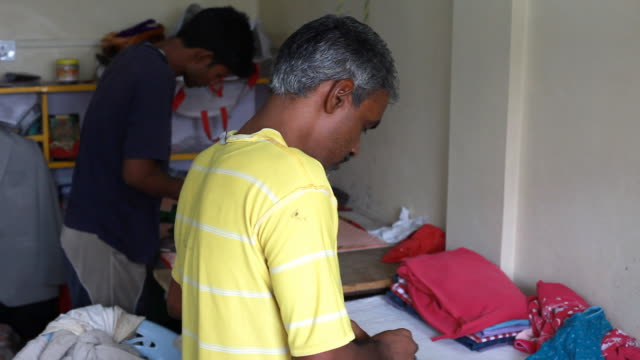 Two men iron clothes in India video