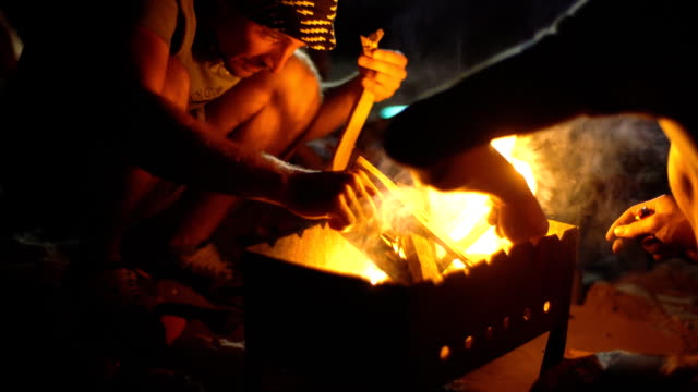 two men kindle a fire - video