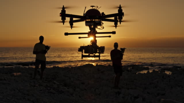 Two men landing a drone on beach at sunset