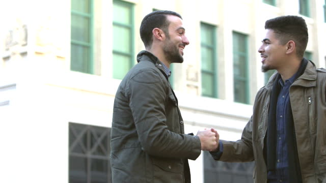 Two men meeting, greeting on city street corner video