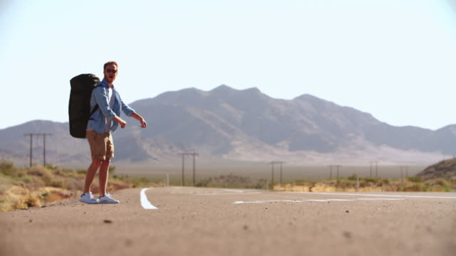 Two Men On Vacation Hitchhiking Along Road Shot On R3D