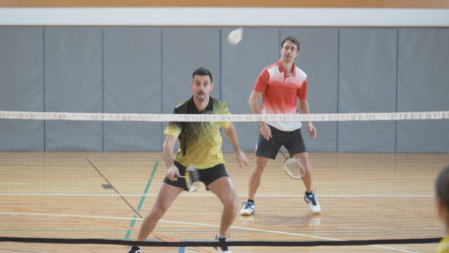 Two men playing doubles indoor badminton against two women video